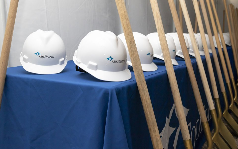 A line of CoxHealth hard helmets and shovels