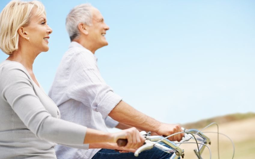 An older couple enjoys biking outside.