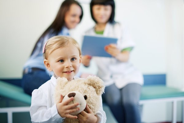 A child sits and holds a stuffed bear.