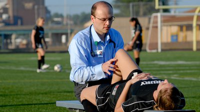A CoxHealth sports medicine physician examines a soccer player on the sidelines of a practice field.