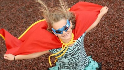 A Children's Miracle Network child wears a mask and cape.