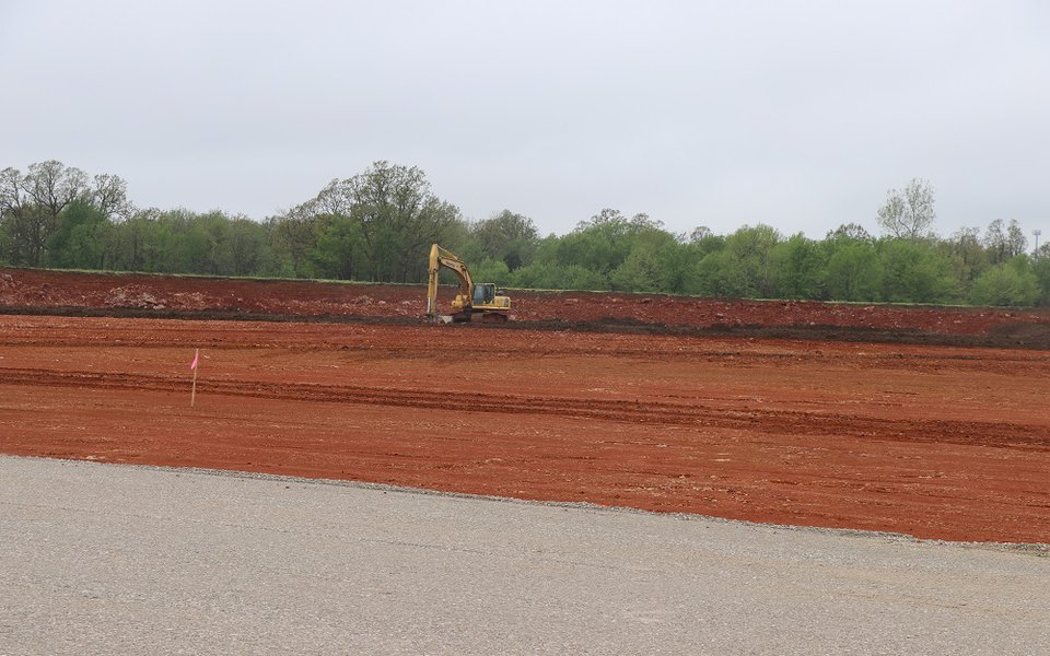 A bulldozer moving dirt to prepare the field for construction