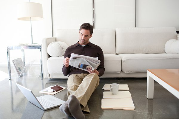 Man on his couch reading a newspaper