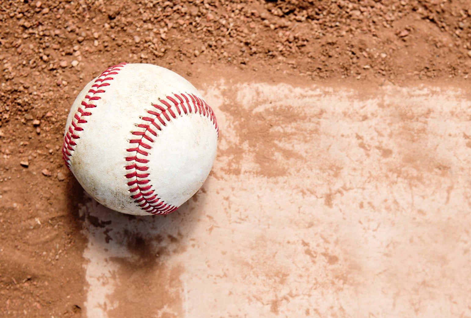 A baseball sits on a field.
