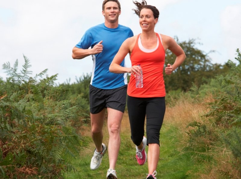 A man and a woman jog down an outdoor path.