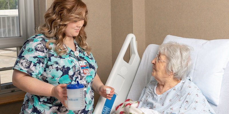 Nurse assists patient with water