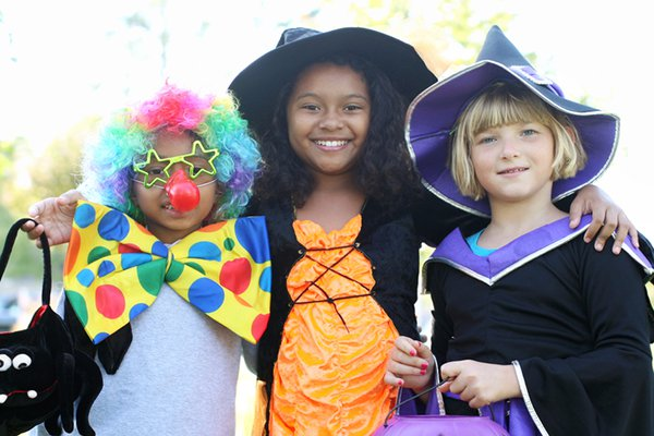 Children smile while wearing Halloween costumes.