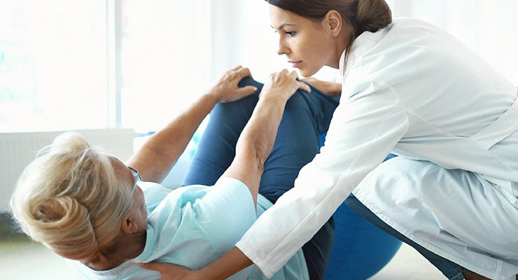 A physical therapist helps an older woman with exercises to improve pelvic health