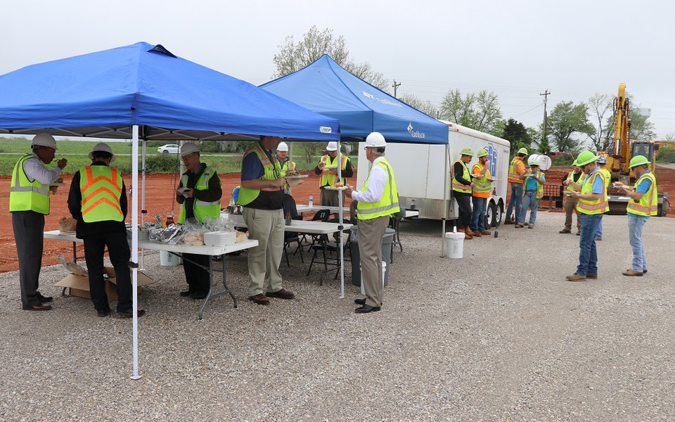 The contractors stand around a work tent having lunch
