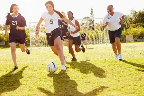 A group of teenage girls play soccer.