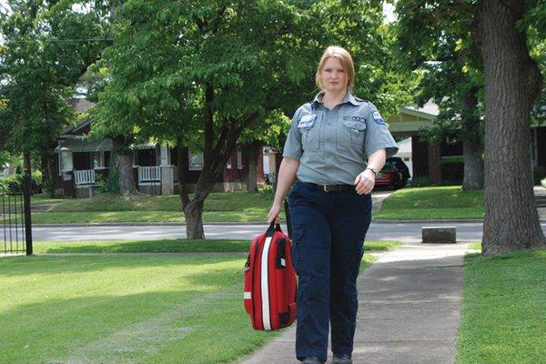 Female paramedic walking on the sidewalk