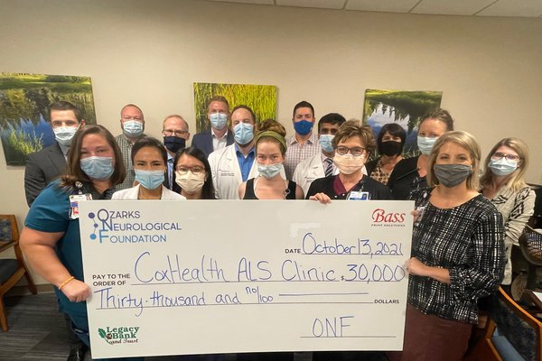 A group stands for a check presentation benefiting the CoxHealth ALS Clinic.