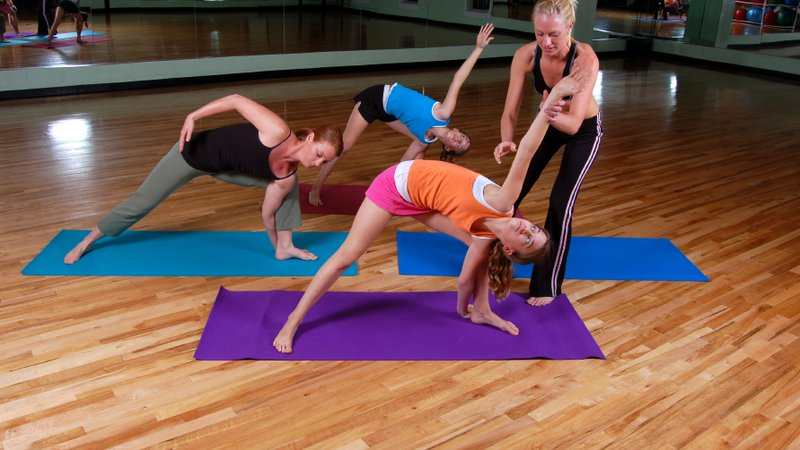 A fitness instructor helps a member perfect a yoga pose.