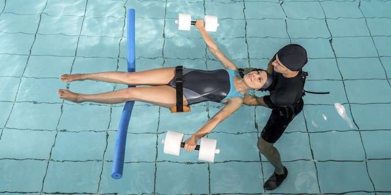 A CoxHealth swim instructor teaches a student.