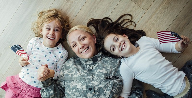 A woman in her army uniform plays on the floor with her two daughters.