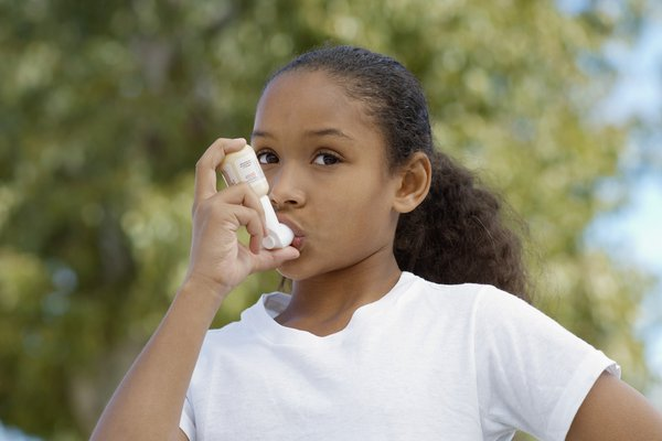 Young girl using her inhaler.
