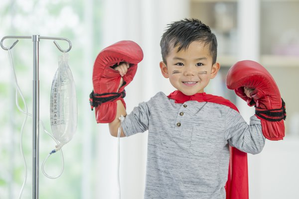 A child stands with a cape and boxing gloves.