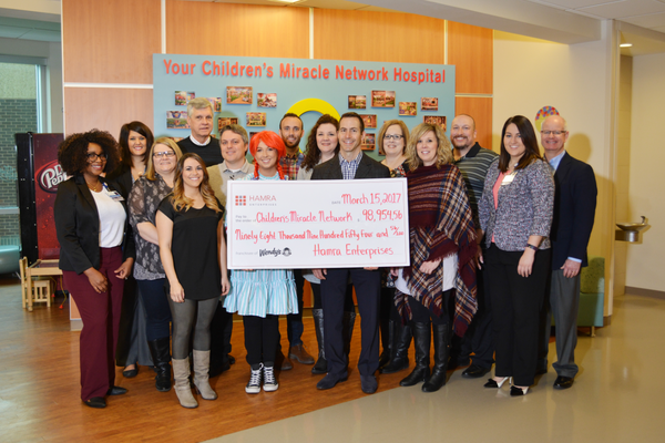 CMH and Hamra hold up a check of the donation.