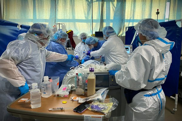 An image shows a team serving a patient in the Cox South COVID unit.