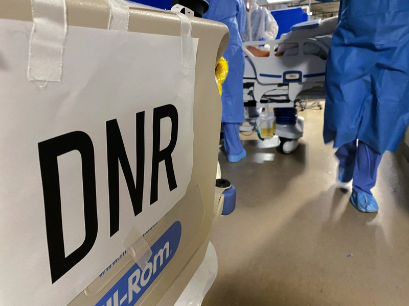 A DNR sign is taped to the end of a bed.