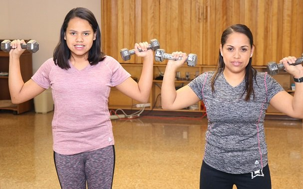 Karyme and her mother are lifting dumbells in CoxHealth's Cardiac Kids program.