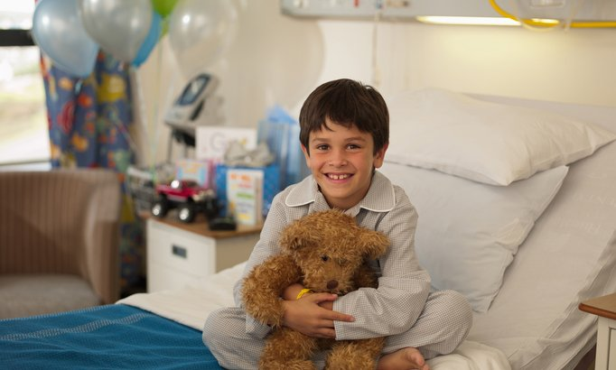 A boy sits smiling in his hospital bed hugging a teddy bear.
