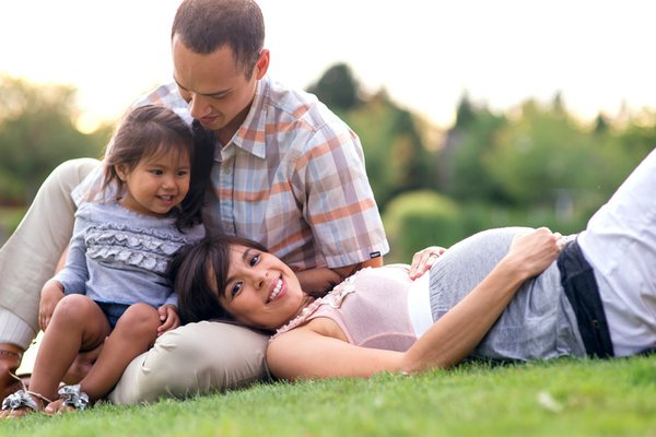 Family of three sit in the grass
