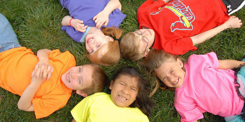 Children of different ages lie on their backs on a field of green grass and smile at the camera.