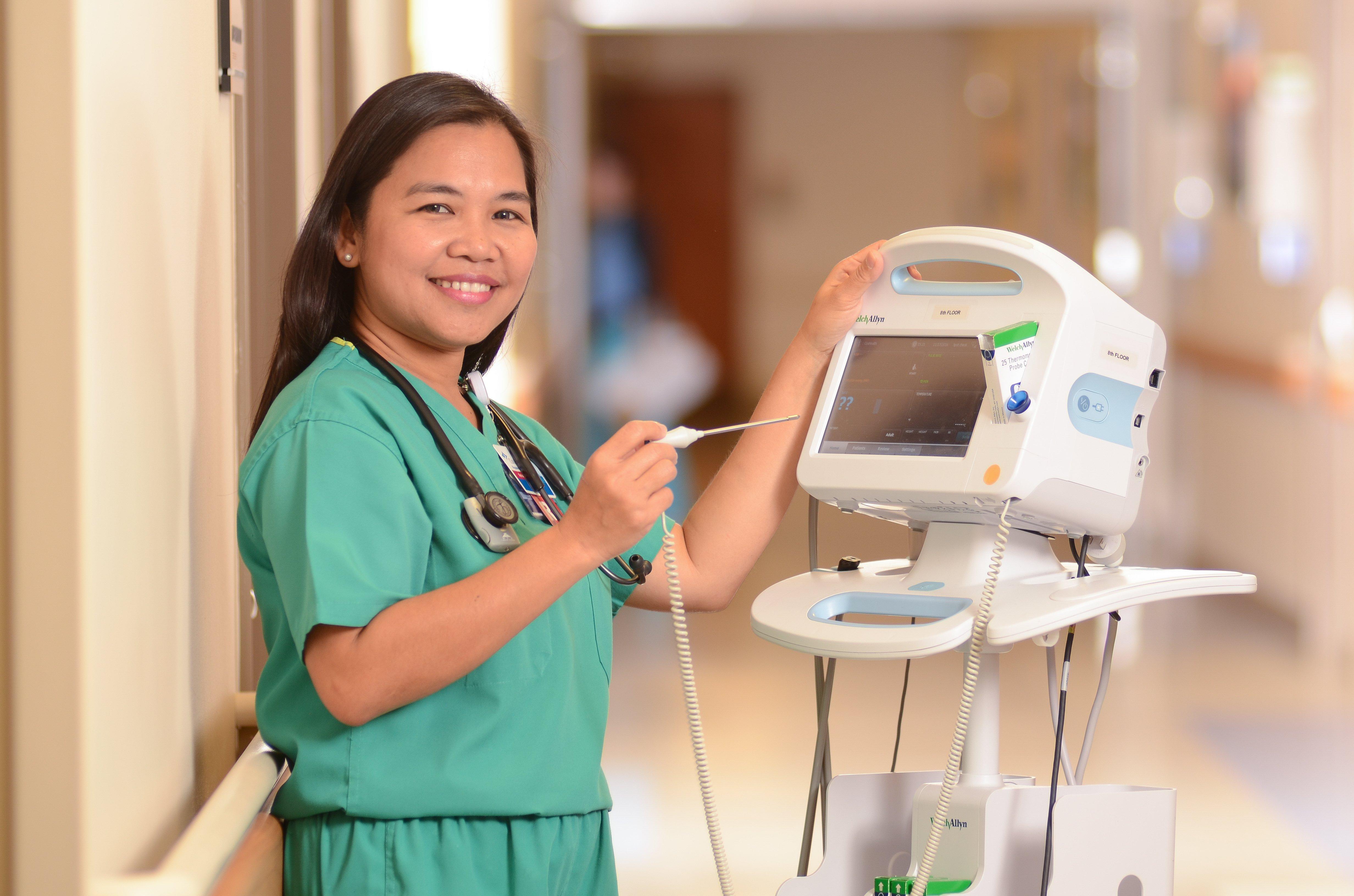 A nurse prepares a thermometer.