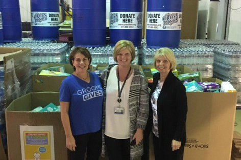 Three woman standing in front of donations.