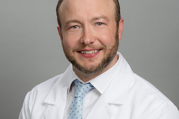 A head shot of Dustin Bartlett shows him in a white coat.