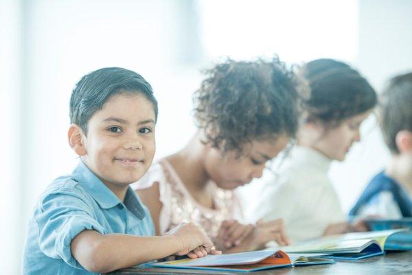 Children reading a book in class