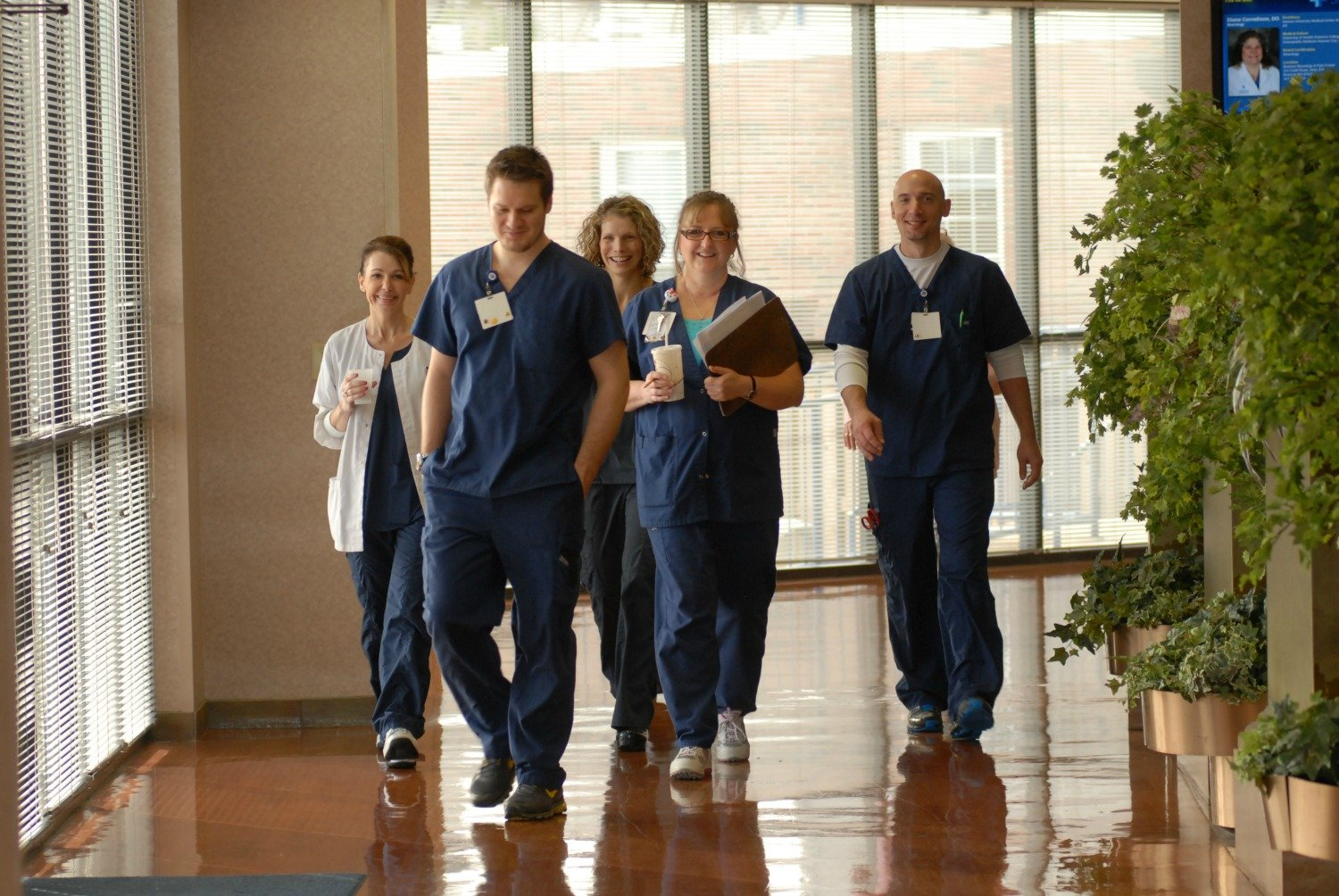 A group of employees walk down the hall.