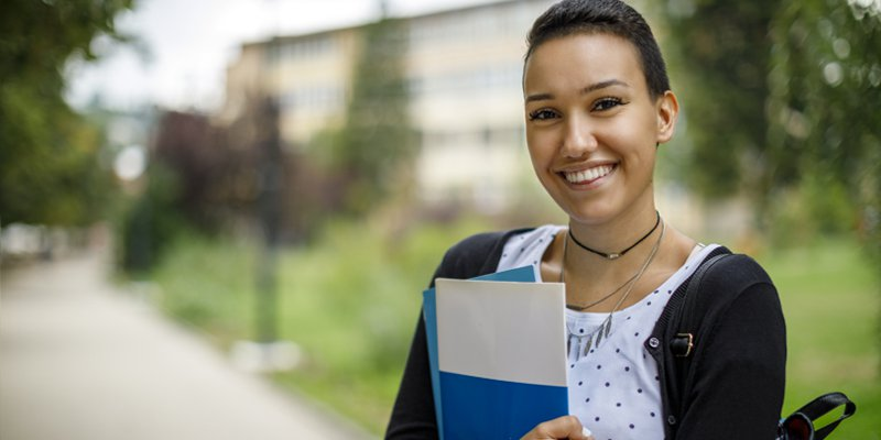 A female college student holding some folders stands and smiles into the camera.