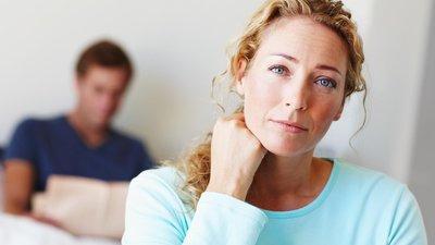 Women looking deep into the camera, nurse looking at paperwork behind her.