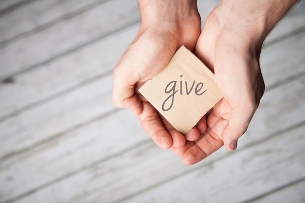 Hands holding a piece of paper that says give.