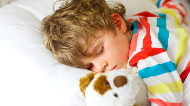 A child cuddles with her teddy bear while she sleeps.