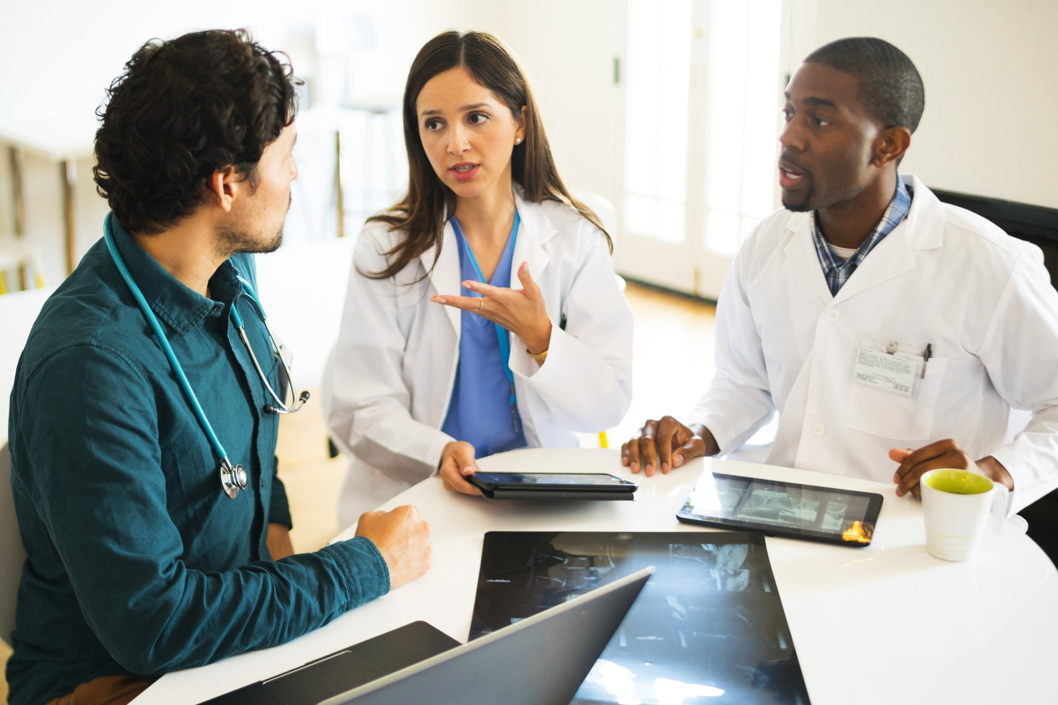 Three students discussing during clinical rotations.