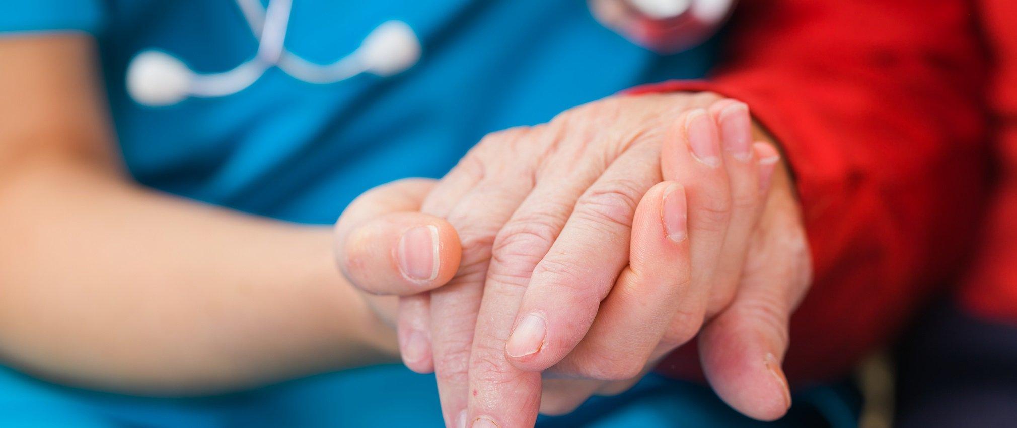 A CoxHealth nurse holds a patient's hand.