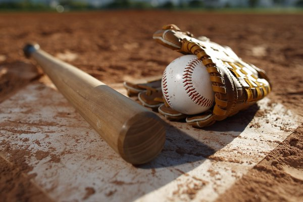 A photo shows a baseball field with glove, ball and bat.