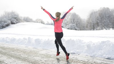 A woman runs in the snow.