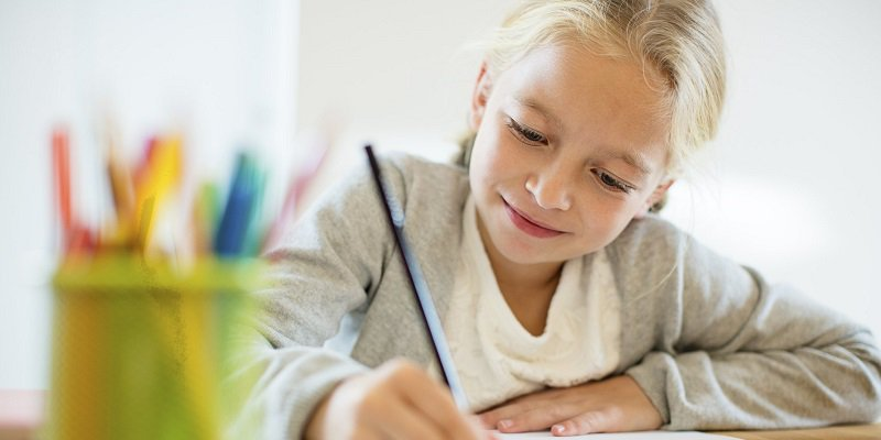 A little girl smiles and writes on a piece of paper.