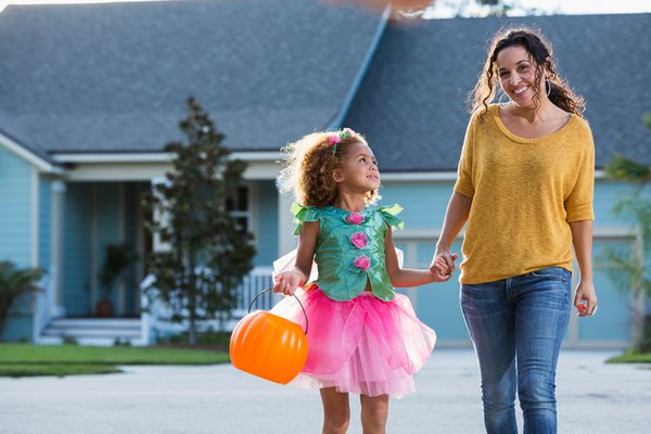 Woman taking her daughter trick or treating