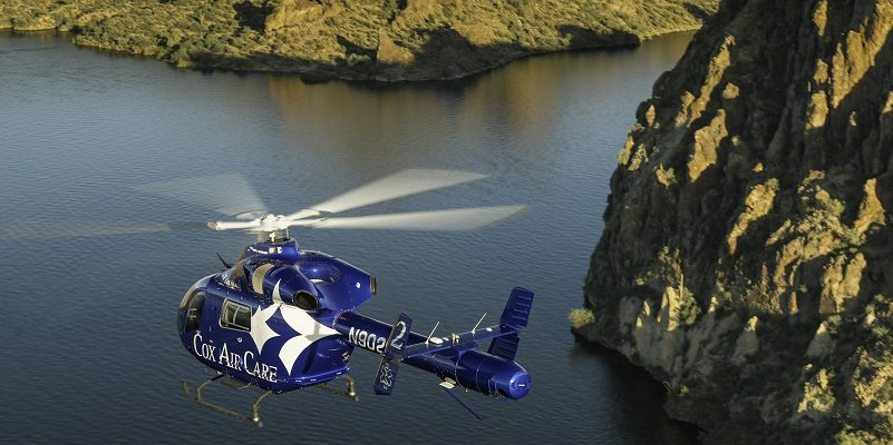A CoxHealth helicopter flies over a lake.