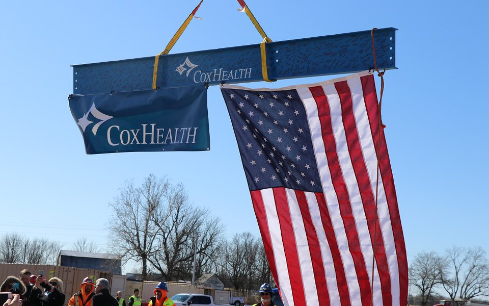 The last beam being moved into place with the American flag and CoxHealth flag attached