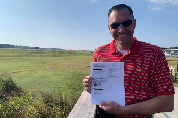 Mathew Michaelson stands with his certification paperwork.