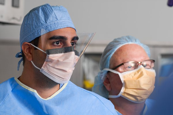 Dr. Kamyab and other doctor in scrubs and masks