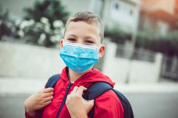 A photo shows a child wearing a mask.