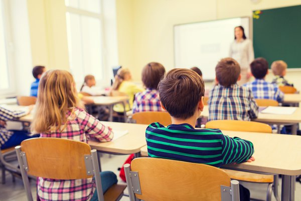 Classroom full of children listening to teacher.
