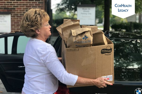 A woman prepares to put Meals on Wheels deliveries in her car.